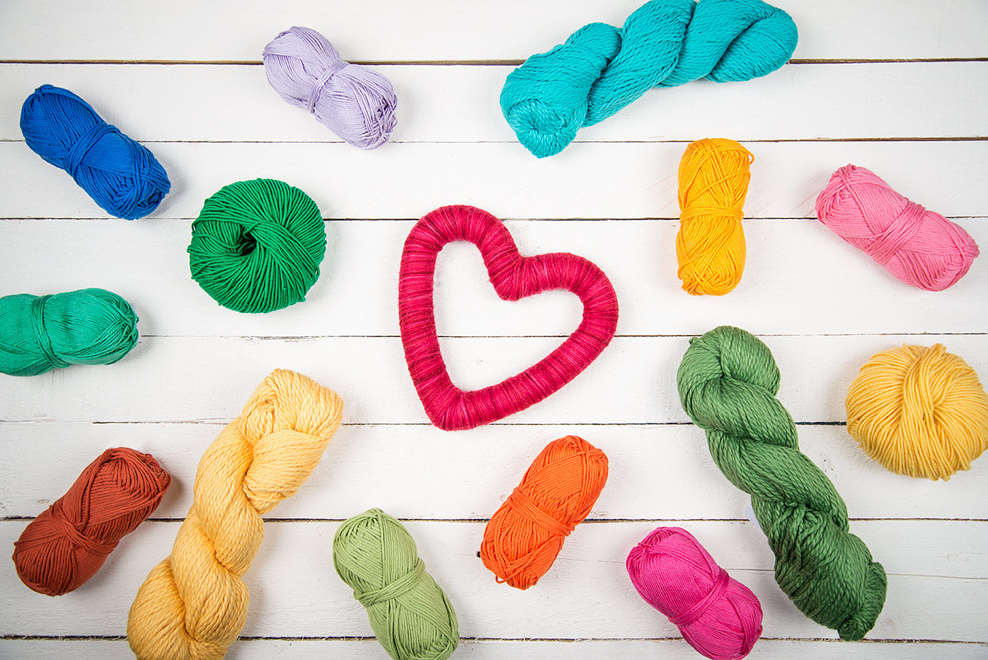 4 benefits of knitting: read more at LoveKnitting (image of bright colored cottons yarns surrounding a yarn heart)